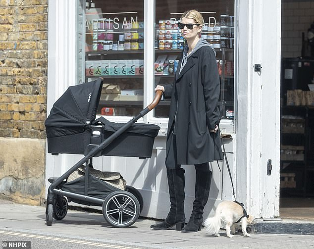 Relaxed: Pixie opted for a casual grey hoodie and a black overcoat as she joined George for the walk with their new baby