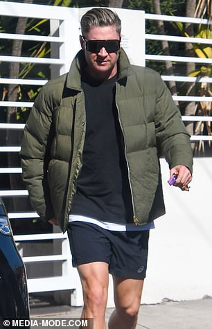 Casual chic: Michael appeared in high spirits for the brief drop-off, wearing a black T-shirt, khaki puffer jacket and black shorts for the occasion
