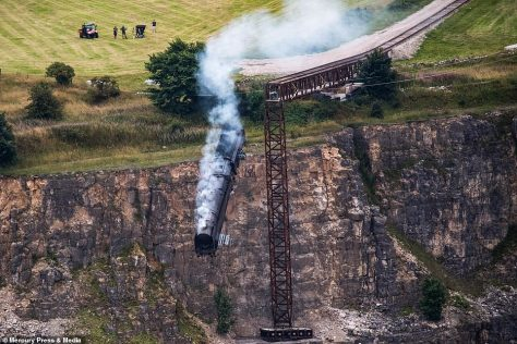 Action-packed: Hollywood actor Tom Cruise, 59, who plays Ethan Hunt in the famous franchise, was reportedly on set as the train went over the edge of the former Darlton Quarry
