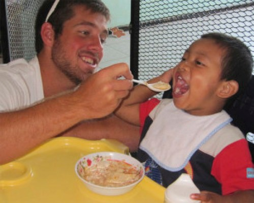 Jordan Differding, FrancisCorps class of 2009, feeds a young child in Alajuela, Costa Rica.