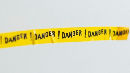 "Yellow tape with the word ""danger"" repeated on it"
