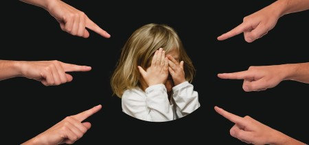 Fingers pointing at a child who is covering her face