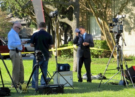 A news crew stands outside