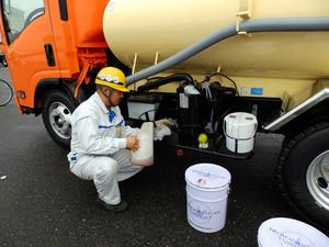 【画像出典:朝日新聞Web】臭いを変える香料入りの潤滑油をバキュームカーに注ぐ様子(提供:東邦車輛)