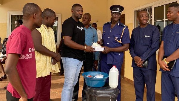 John Dumelo donating items to the Ayawaso West police officers