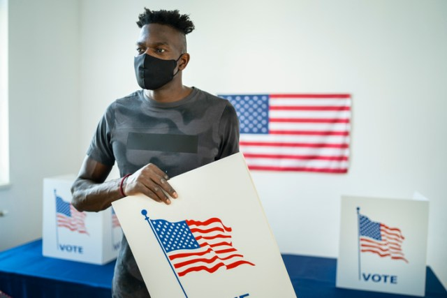 Young afro-American volunteer preparing the voting booths for Election Day