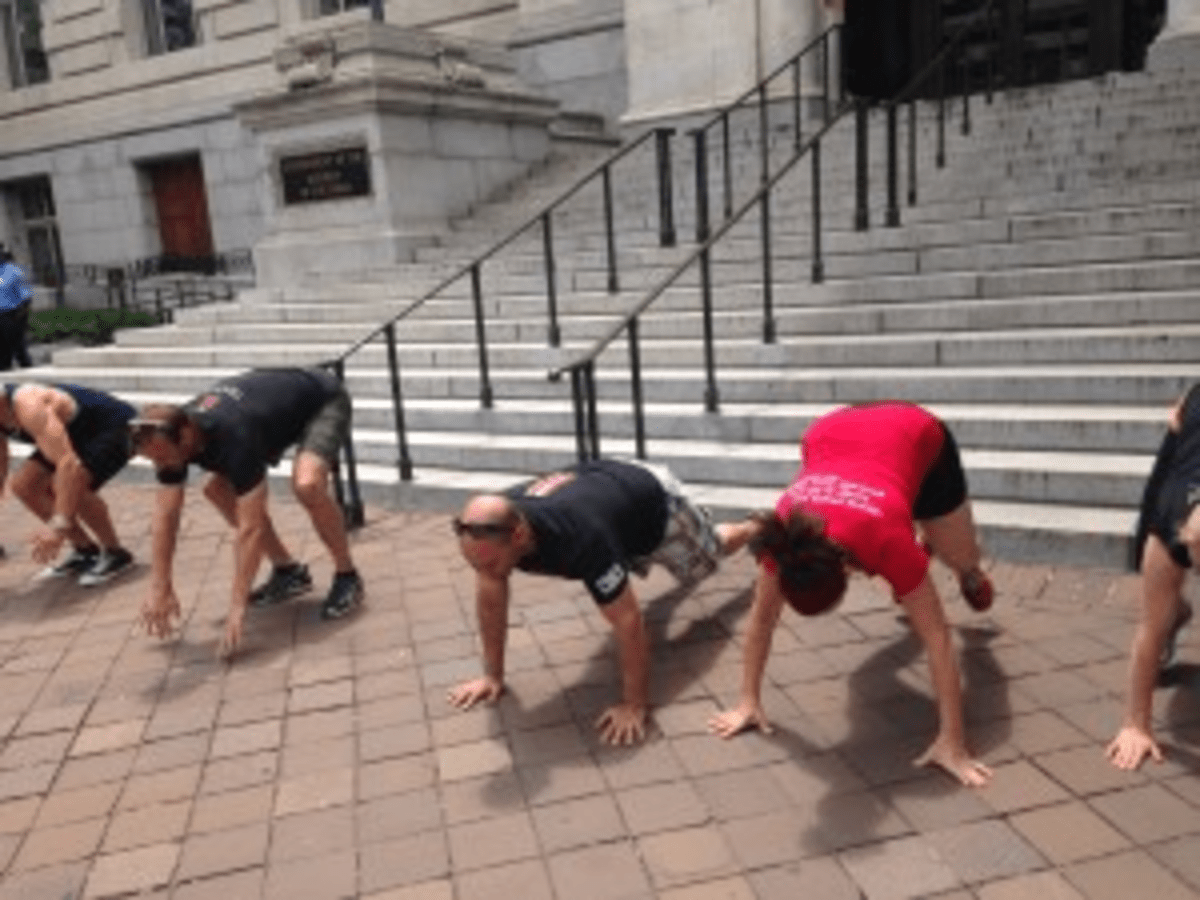 Fitness enthusiasts perform burpees to protest the yoga tax on June 3