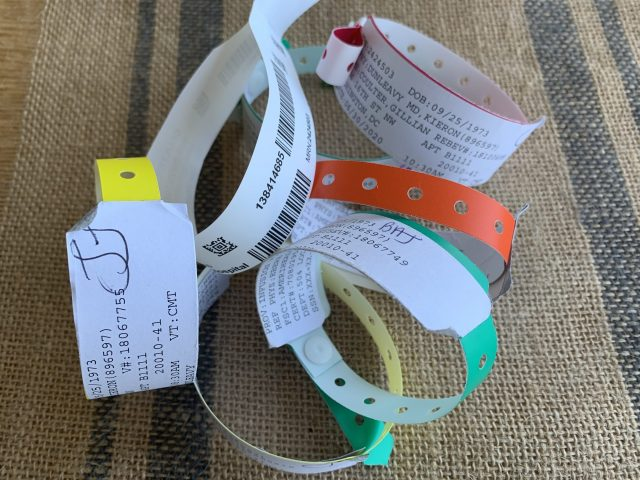 A string of different color hospital wristbands