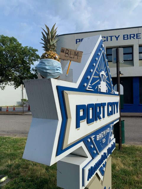 The Port City Brewing sign with a pineapple wearing a mask