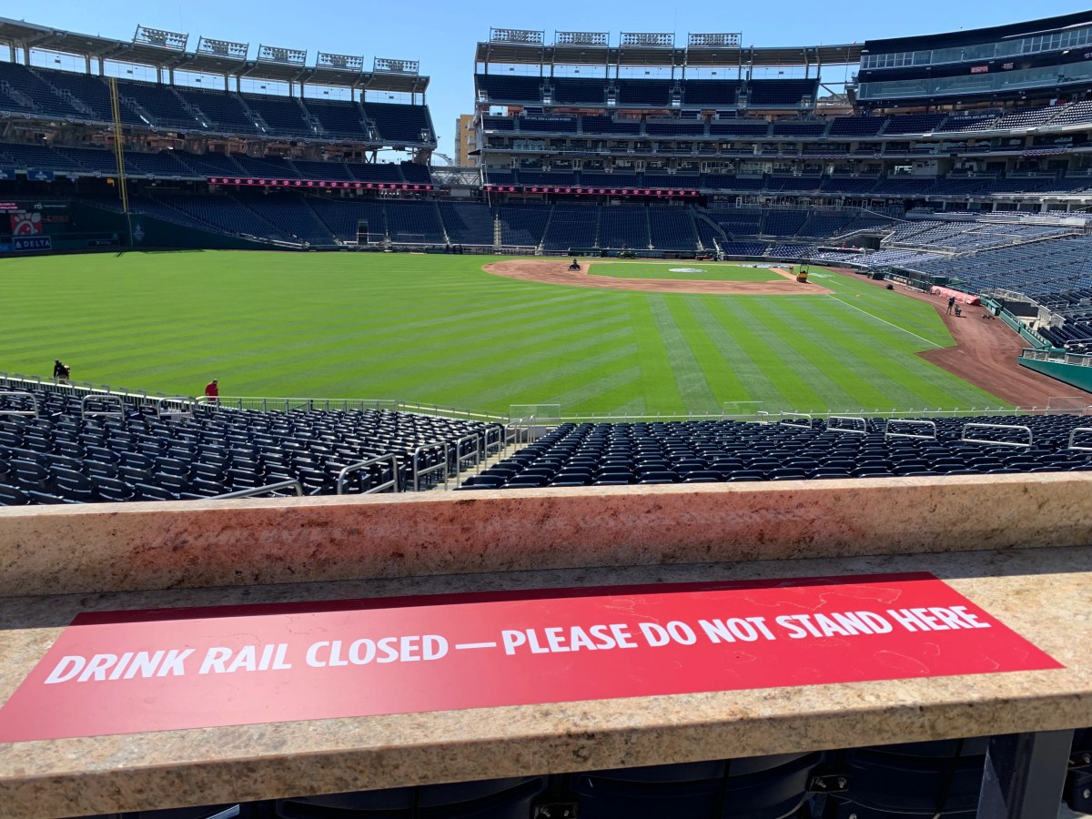 A sign at Nationals Park advising fans not to stand or rest their drinks on a rail.