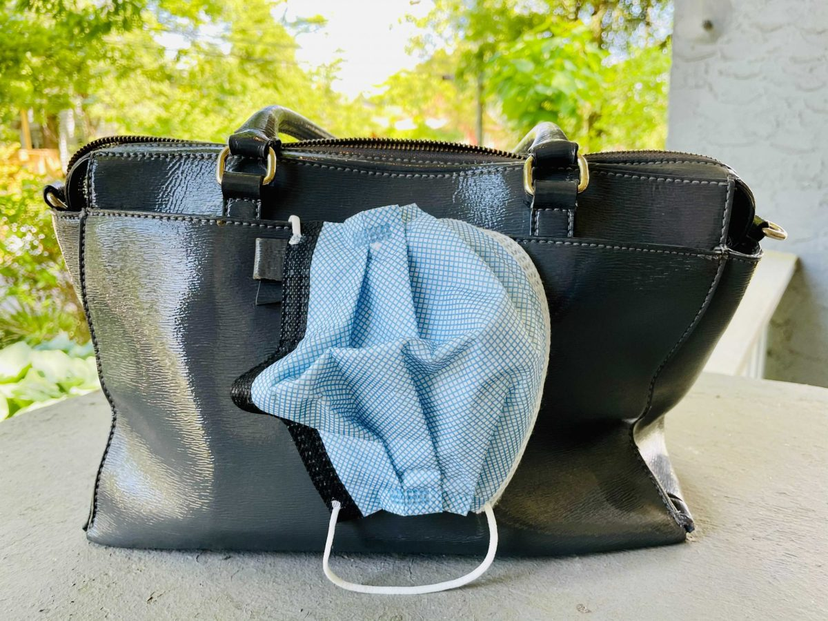 A light blue mask sticking out of a purse