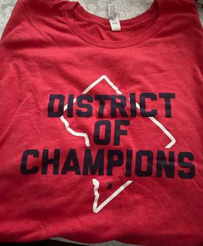 """A red t-shirt reading """"District of Champions"""""""