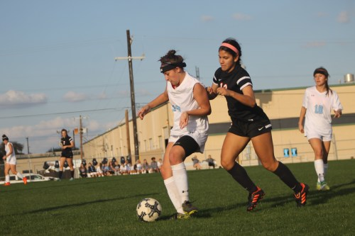 Sophomore Katelyn Stamps advances the ball with a defender on her back. Photo by Meredith Kershaw.