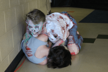 Student is grabbed and pulled down the hallway by a lurking monster.