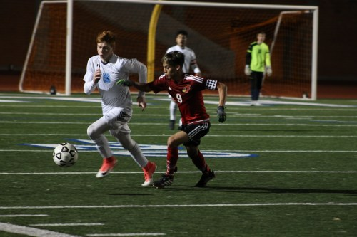 Junior Josh Maskill chases the ball as a defender rushes behind hm. Photo by Nayala Summons.