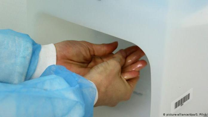 A hospital worker using alcohol based hand disinfectant (picture-alliance/dpa/S. Pilick)