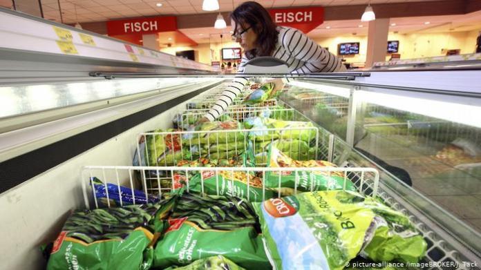Woman reaches into supermarket freezer