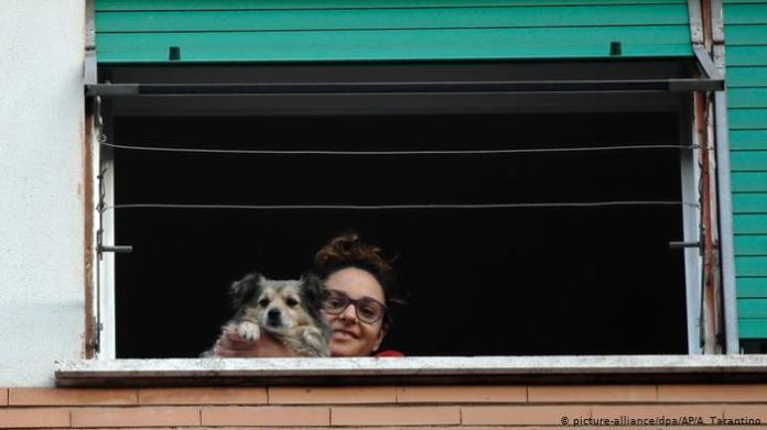 A woman holding her dog up to the window in Italy