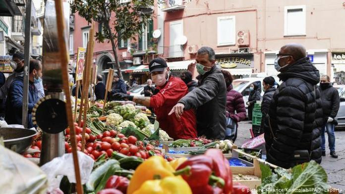 People shopping for fresh vegetables at an outdoor market