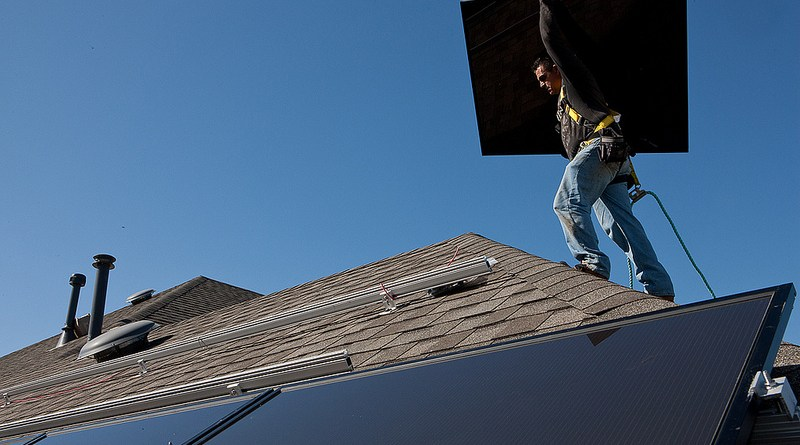 (Image) A local installer adds photovoltaic solar panels to the roof of a San Antonio home