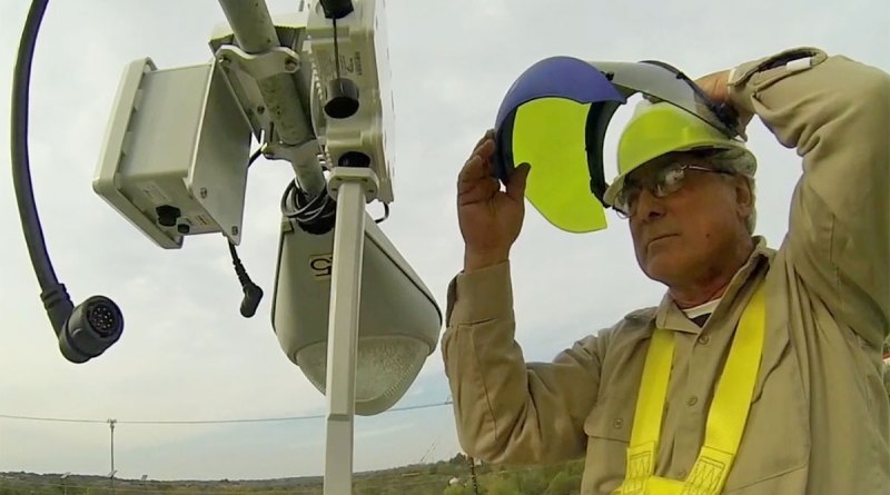 (Image) A subcontractor installs one of the devices that will make up the network canopy for the smart grid.
