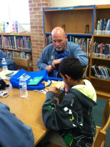 (Image) Russ Coons presents his Reading Buddy with his summer backpack filled with books and activities.