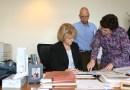 (Image) Ricardo Diez and Vicki von Scheele of CPS Energy's debt management area meet with their senior director, Linda Dzierzanowski, to review a bond offering document.
