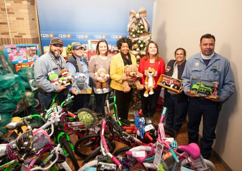(Image) President & CEO Paula Gold-Williams (Center) joins Maria Garcia, Vice President of Community Engagement, (Center Right) and other employees to show off mounds of toys employees collected for Angel Tree.