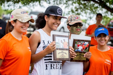 (Image) Volunteers celebrate a fun day of fishing with participants at last year's Kids Fish Day. Each participant was awarded a special plaque with a picture of their catch.