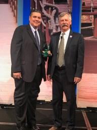 (Image) Community Programs Director Jesse Hernandez accepts the award from Rod Litke, CEO of CS Week.