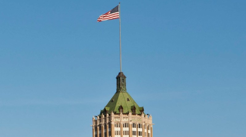 US flag flying high at a downtown building