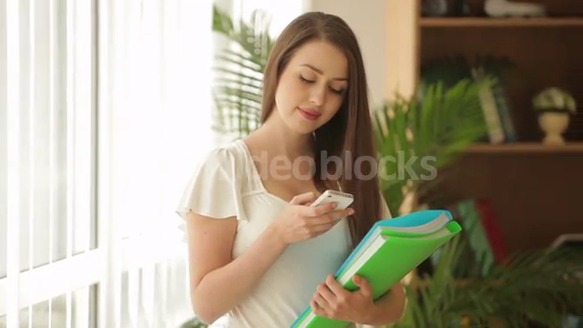 pretty-young-woman-standing-in-front-of-window-holding-paper-folders-using-_4y5xxthrg__PM13-07-52