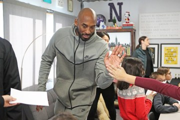 Kobe gives a high five to student as he leaves the classroom.