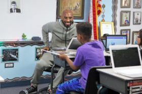 Kobe Bryant sits in chair chatting with student