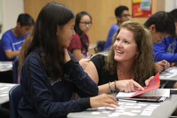 teachers works with student at during classroom lesson