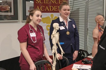 two students stand over a table with models of a human skeleton and other medical models