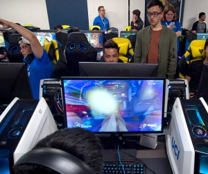 students gather around computer monitors to play video games