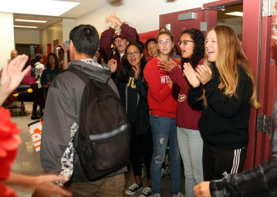 Students cheer a senior on campus