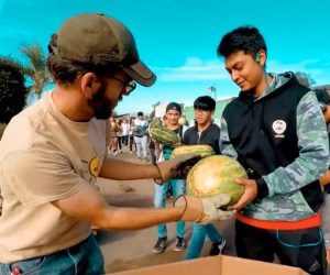Student hands teacher a watermelon