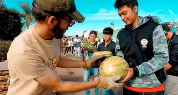 Student hands teacher a watermelon