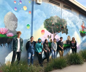 Students stand in front of a mural