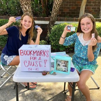 Two students selling bookmarks outside