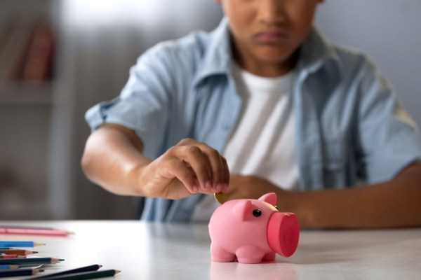 Kid filling piggy bank