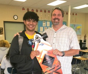 A student and teacher, holding a skateboard