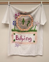 a t-shirt with an anti bullying message hangs from a wall