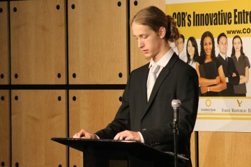 Student Victor Valenzuela pitches his business idea at a podium