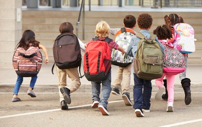 A group of students run toward their elementary school