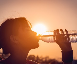 Female drinking a bottle of water with sun in the background