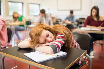 student sleeps on her desk in a classroom