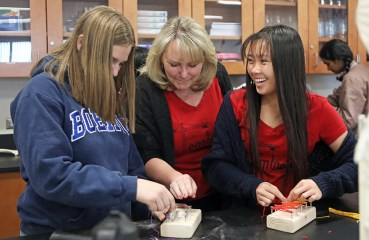 two students work on an engineering project with the help of their teacher